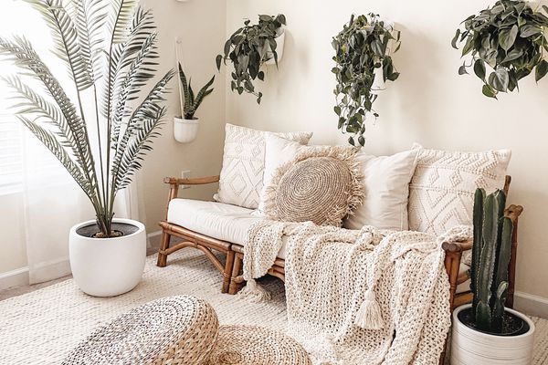Faux plants throughout this living room with a neutral boho decor