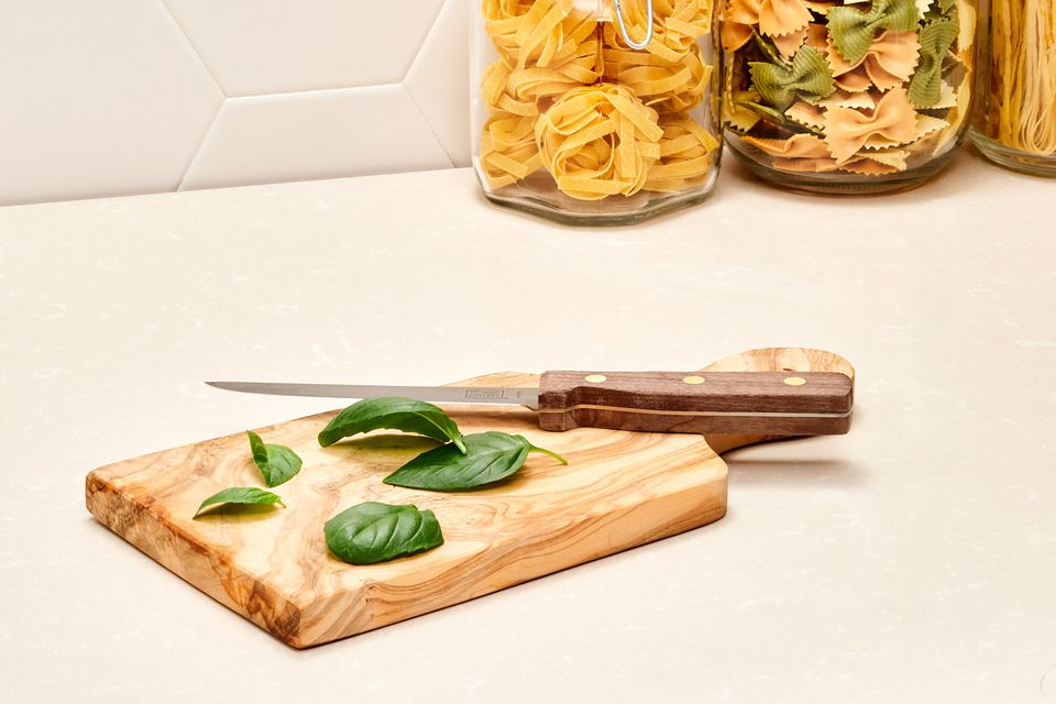 chopping basil on a cutting board in the kitchen