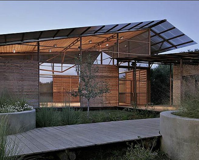 Raised wooden walkways in front of a modern house built on platforms