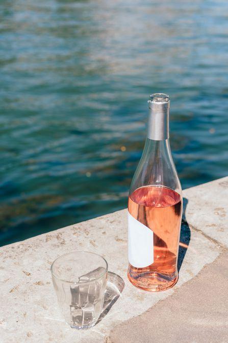 Botella de rosado con un vaso en la repisa de la piscina