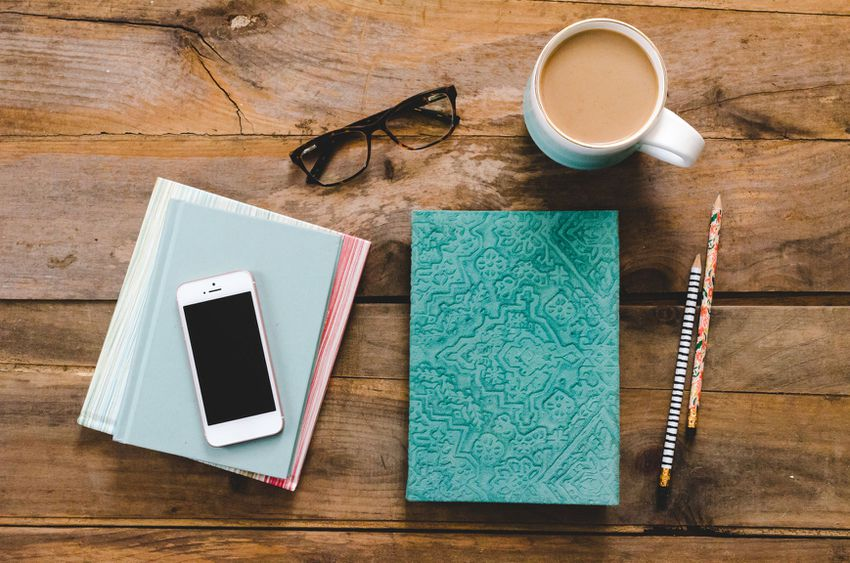 Wedding planner, mobile phone, notebook, glasses, coffee