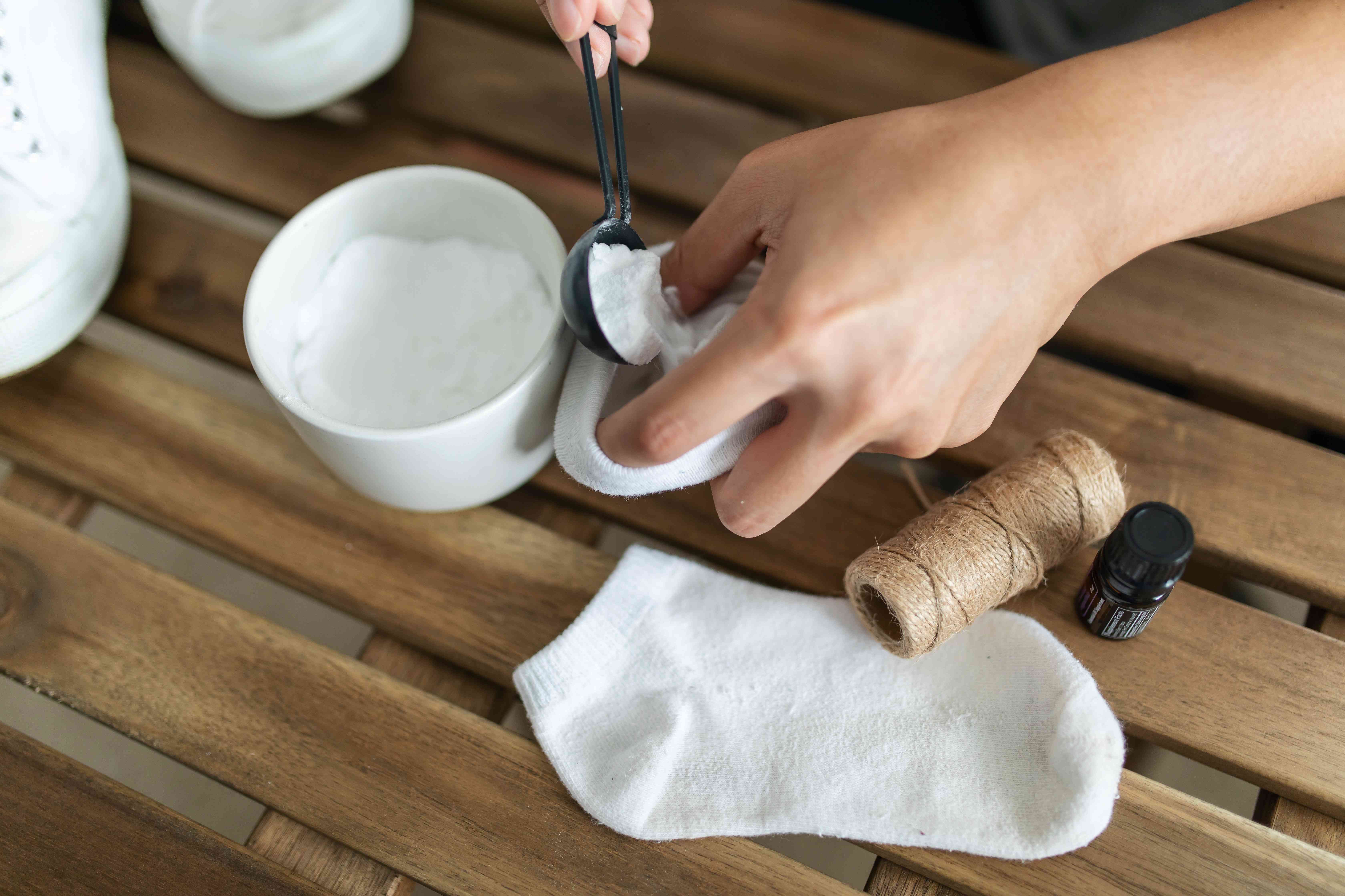 person filling a sock with baking soda