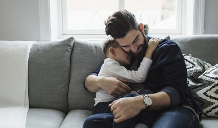Father and young son hugging on couch.