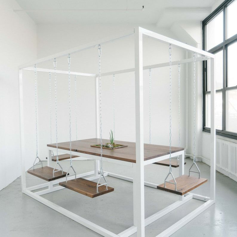 a dining table consists of suspended chairs swings and a suspended table
