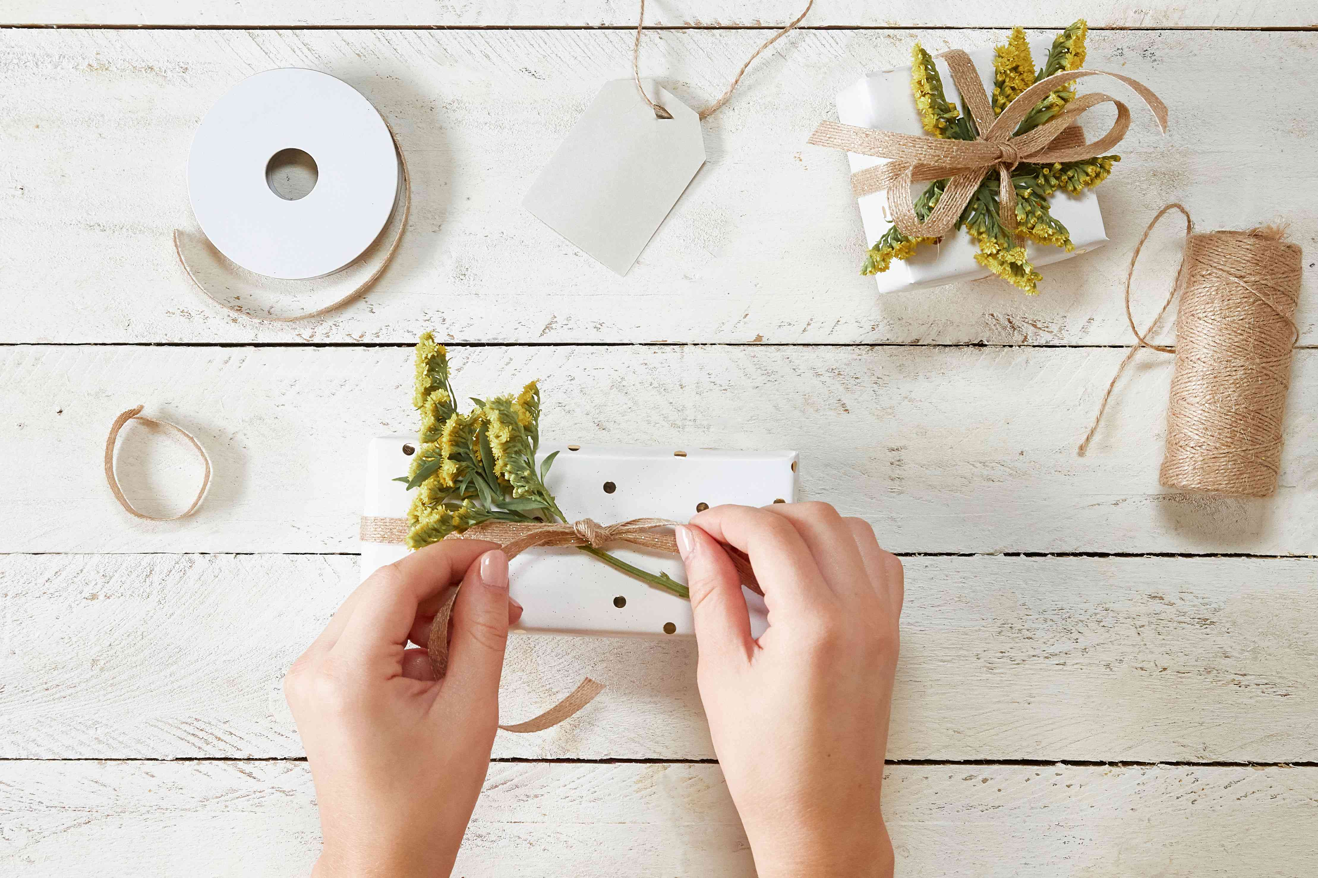 Woman's hands tying herb on present top