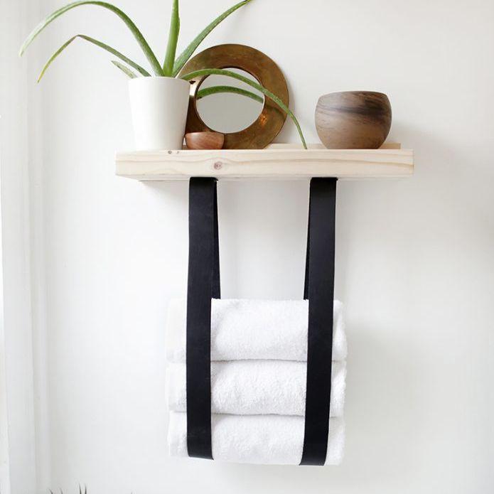 Un estante de madera con toallas colgando de él
