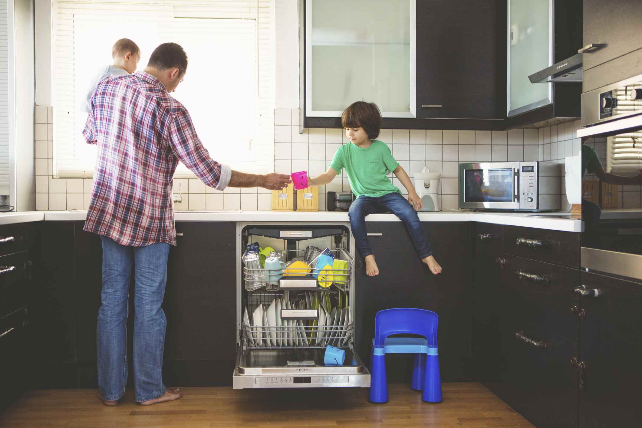 Father and son loading dishwasher