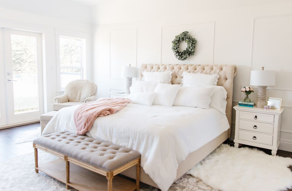 a neutral bedroom features a bed with white bedding