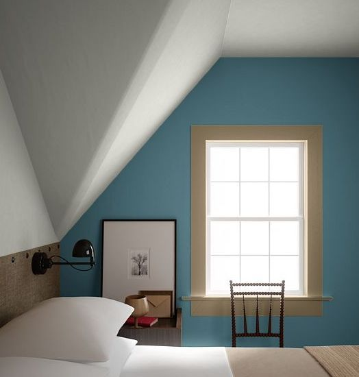 A bedroom with a white ceiling and soft blue walls