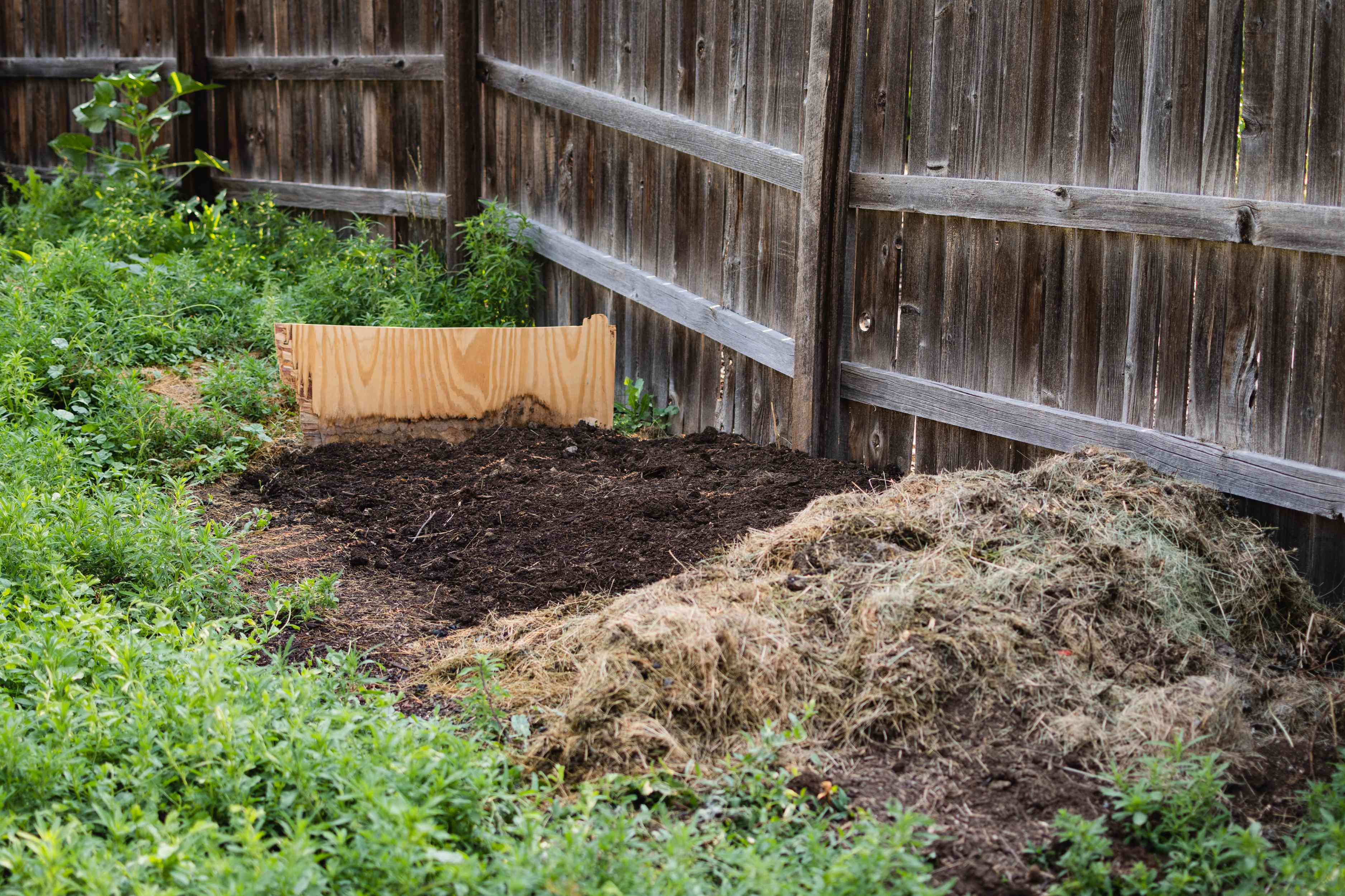 Composting pile location in backyard next to wooden fence