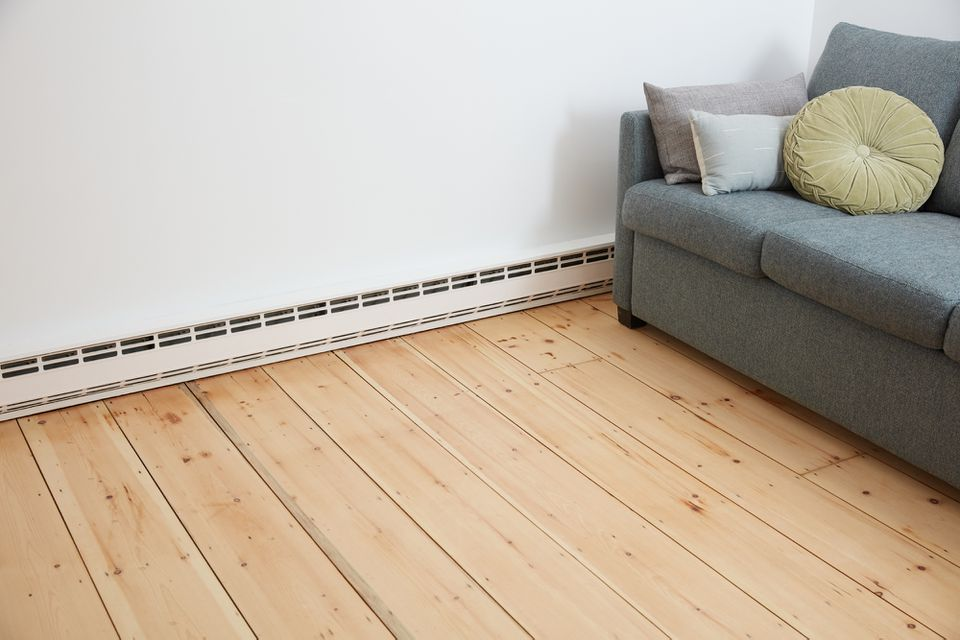 Electric baseboard heater next to gray sofa on wooden floors