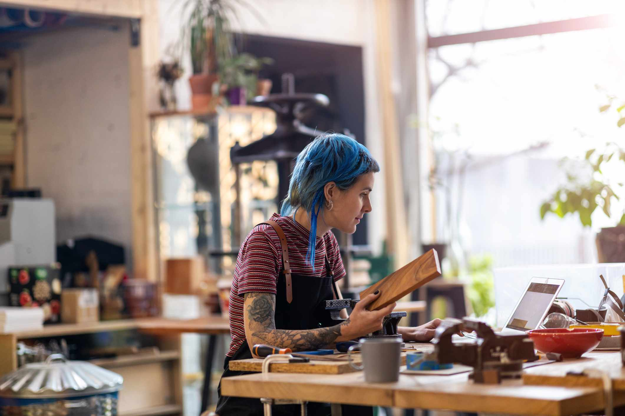 A woman with blue hair in an art studio.