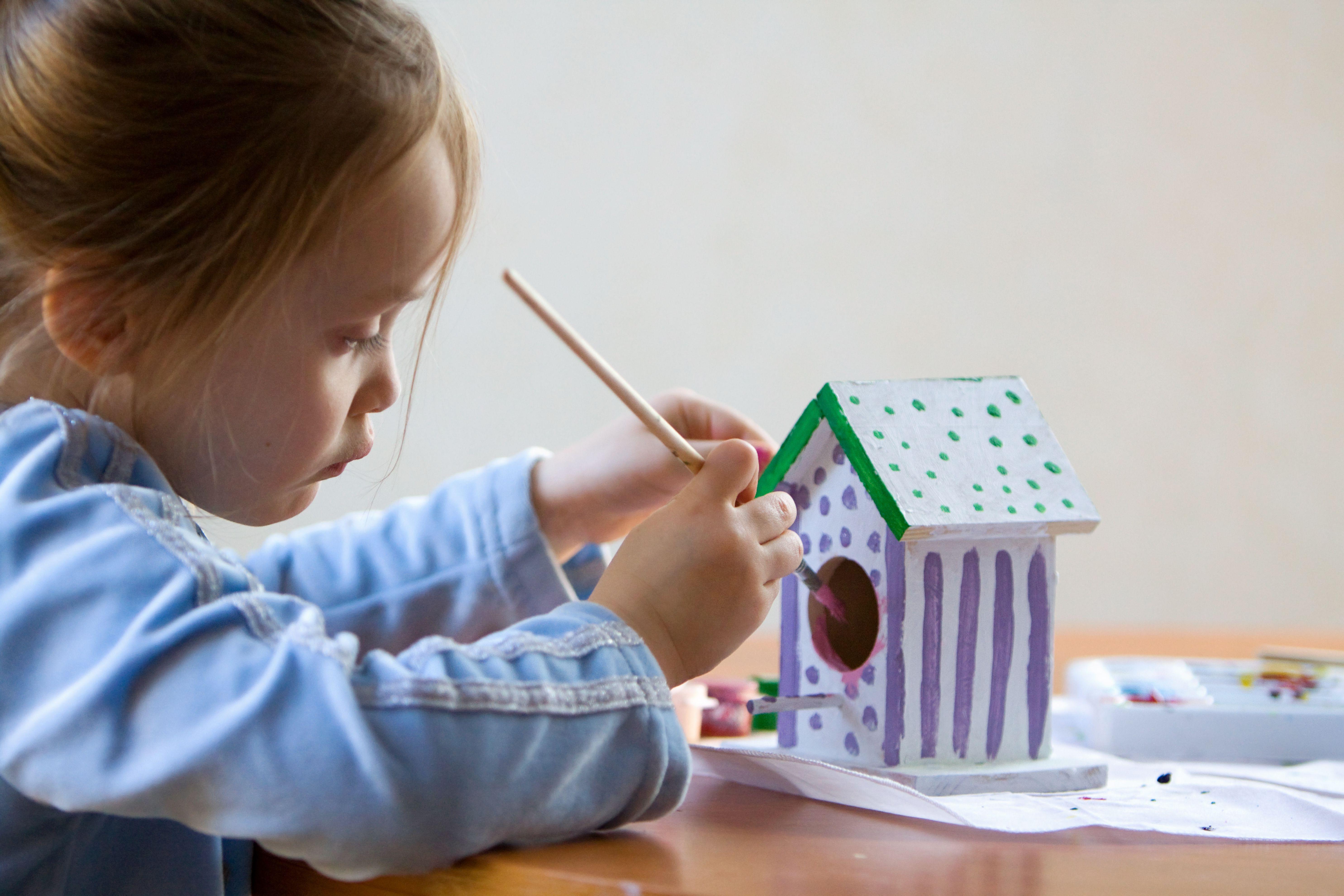 Little girl painting wooden birdhouse