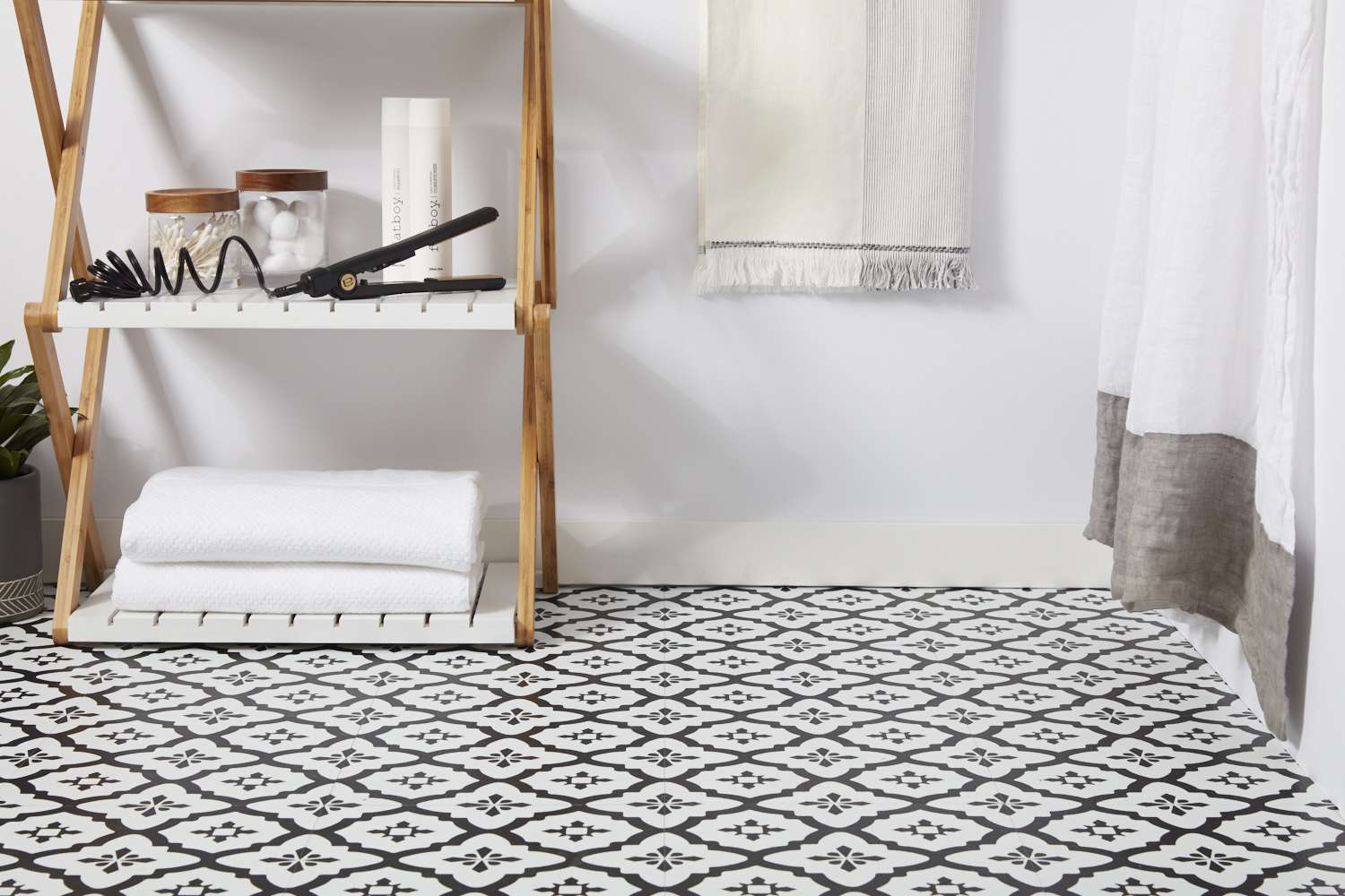 Vinyl tile flooring with wooden stand and bathroom items above folded white towels