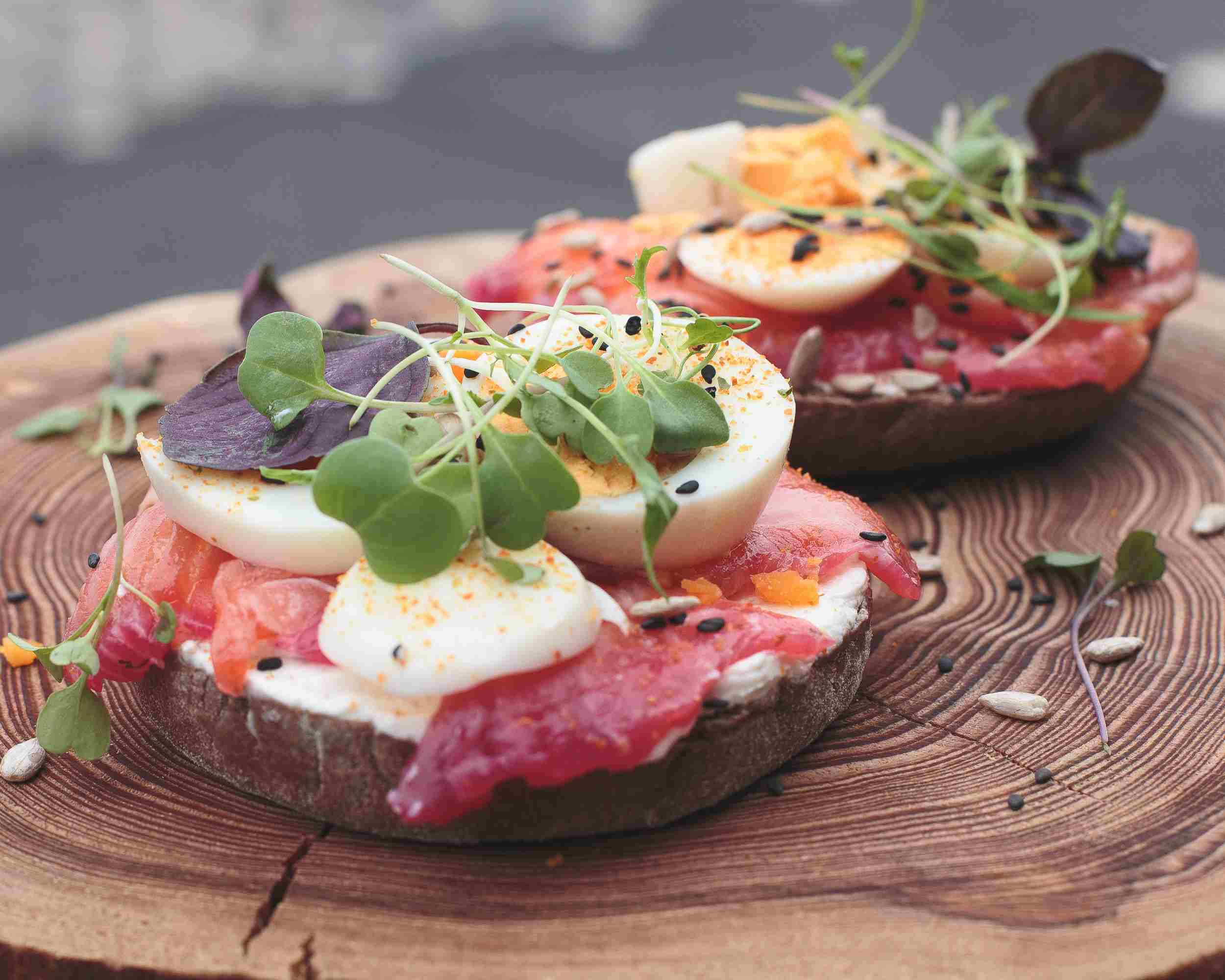 Salmon and egg sandwich on a tree stump platter.