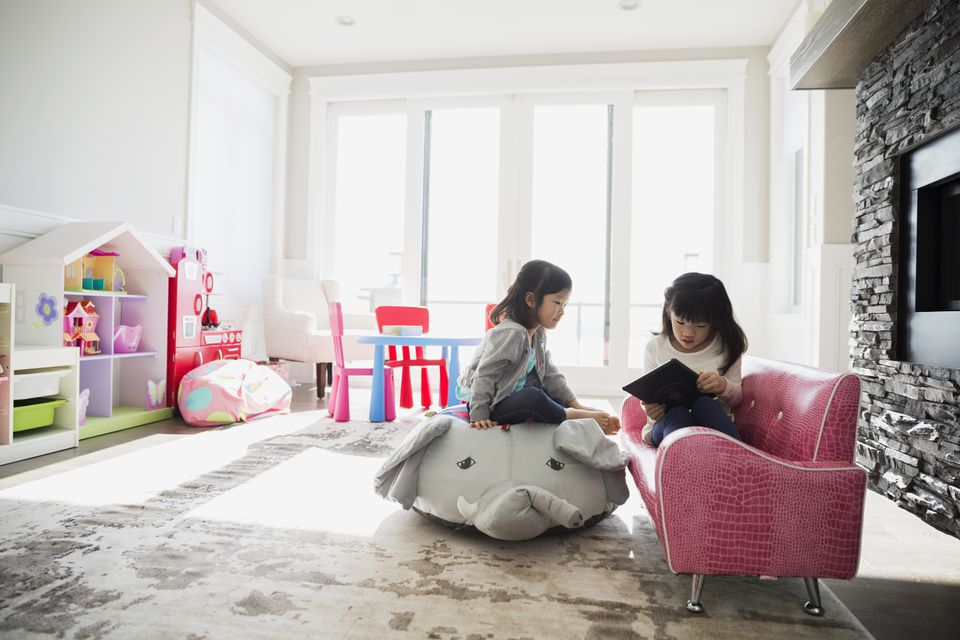 Two girls with tablet in modern playroom
