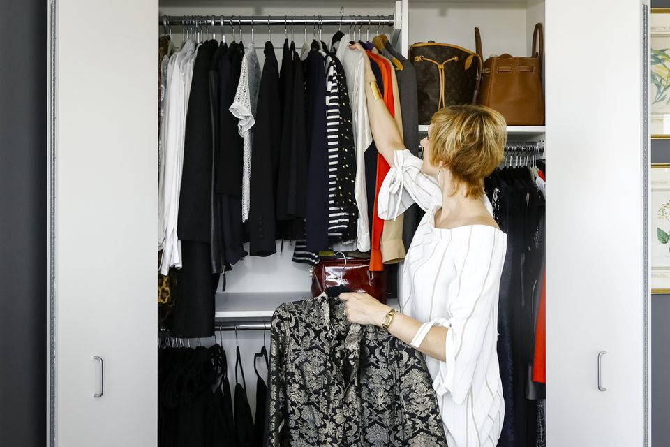 Woman hanging clothes in a closet.