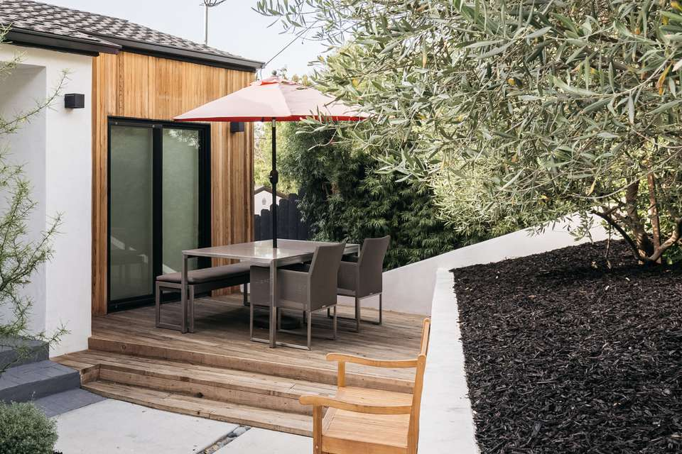 Composite deck with umbrella over patio table and chairs near trees