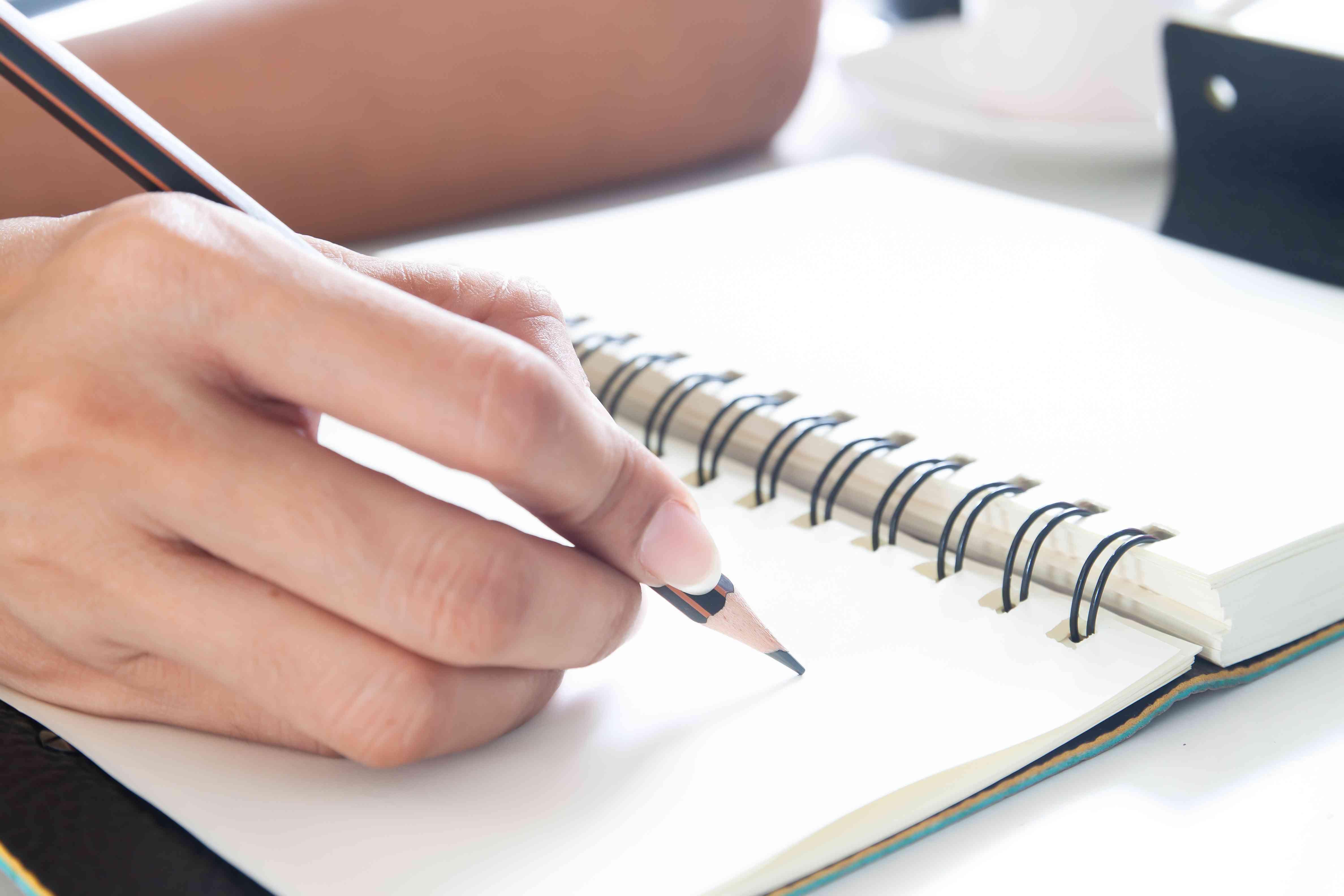 mujer escribiendo con un lápiz