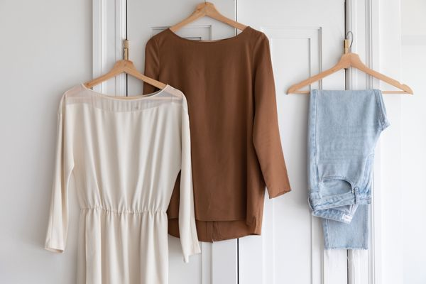 Cream colored dress, brown long sleeved shirt and folded jeans hanging on wooden hangers