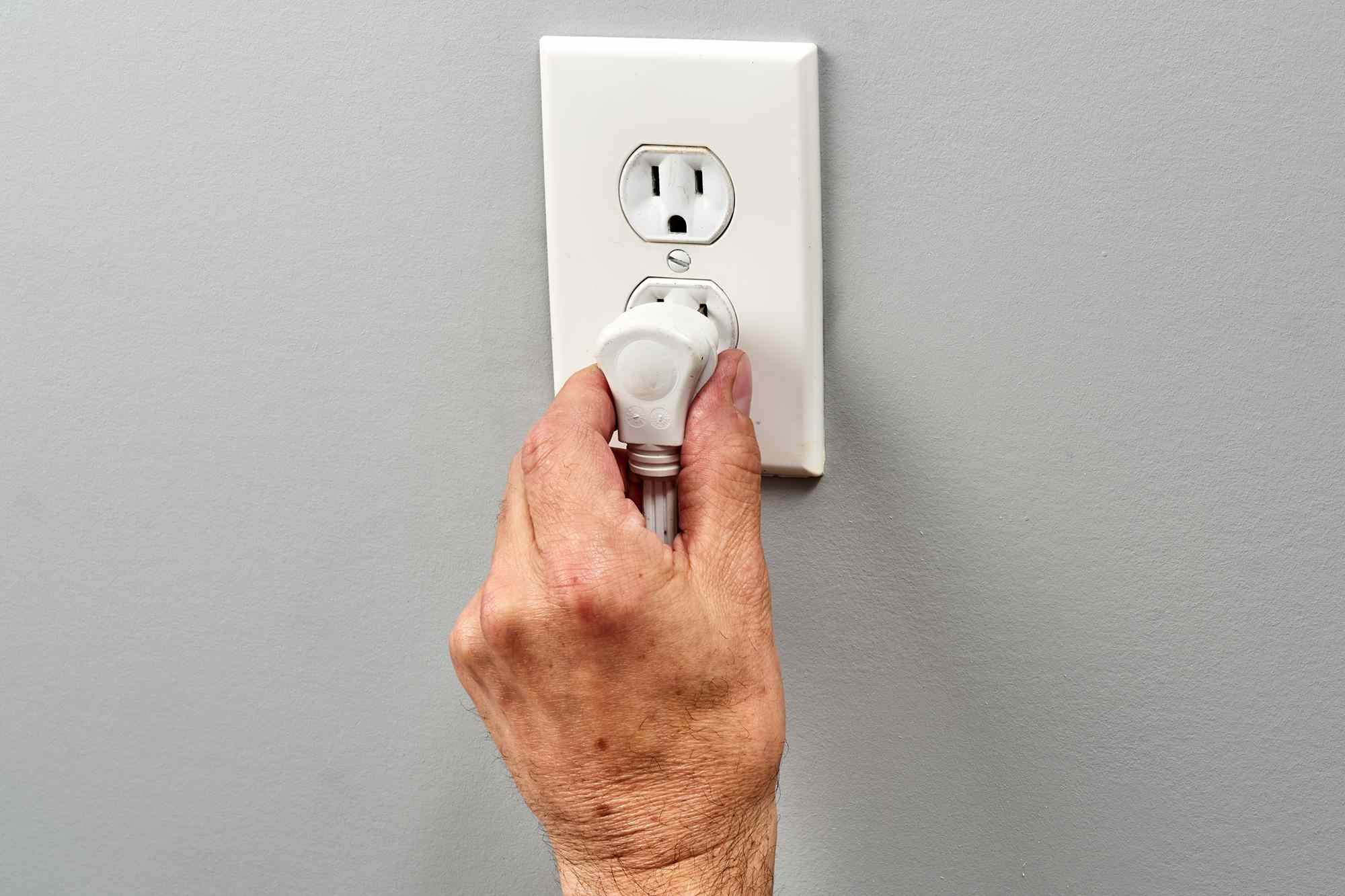 Cord unplugged from warm wall outlet by hand