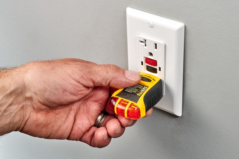 Yellow voltage tester inserted into wall outlet