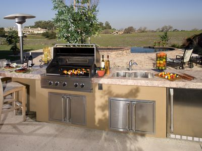 Outdoor kitchen with grill, counter top and chairs.