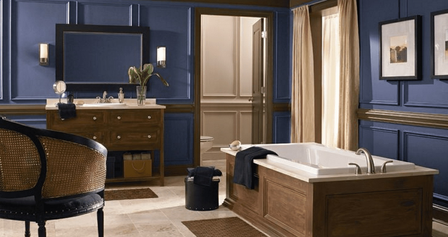 A massive, luxurious blue bathroom with bathtub, drapes across the window, vanity, and mirror.