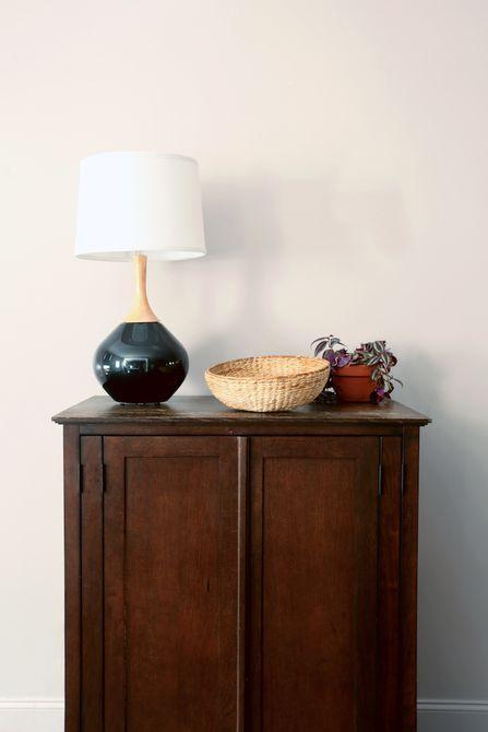 Lámpara, canasta y planta encima de una madera gabinete