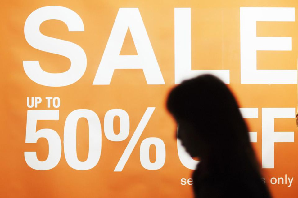 Poster with message 'Sale up to 50% off' in shop window, passerby silhouette in foreground