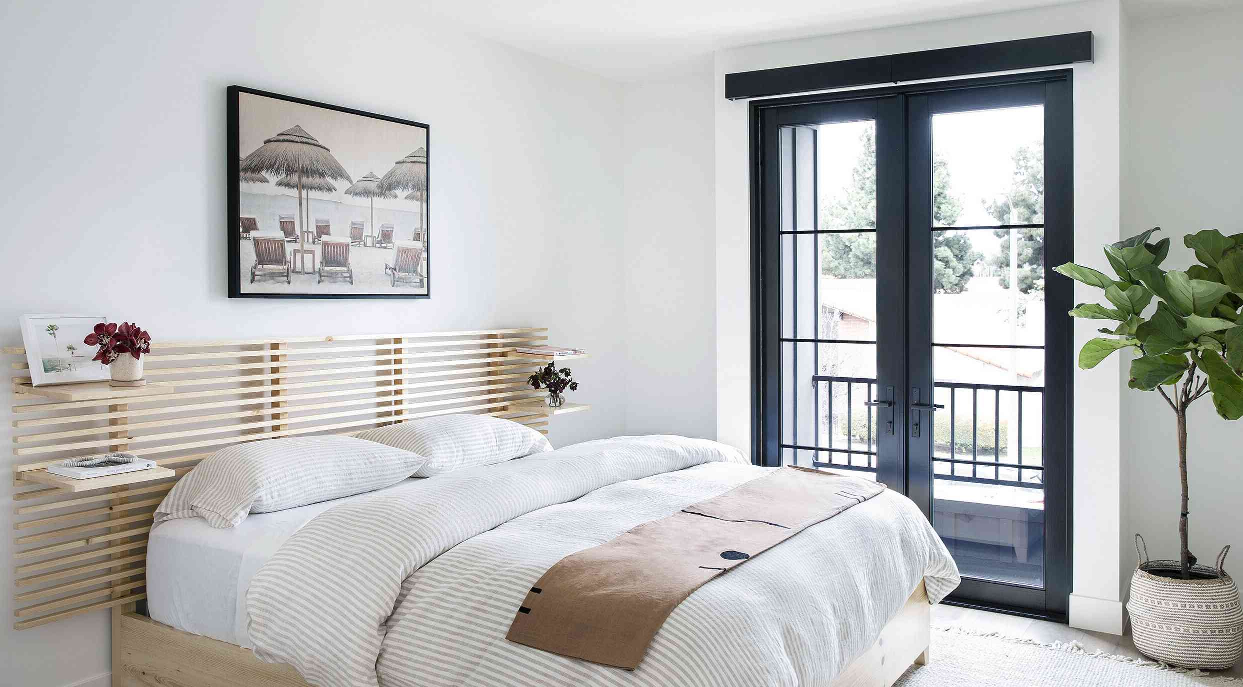 bedroom with white walls and bedding, floating shelves attached to headboard