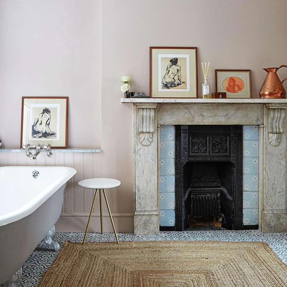 Bathroom with a fireplace and a light pink wall
