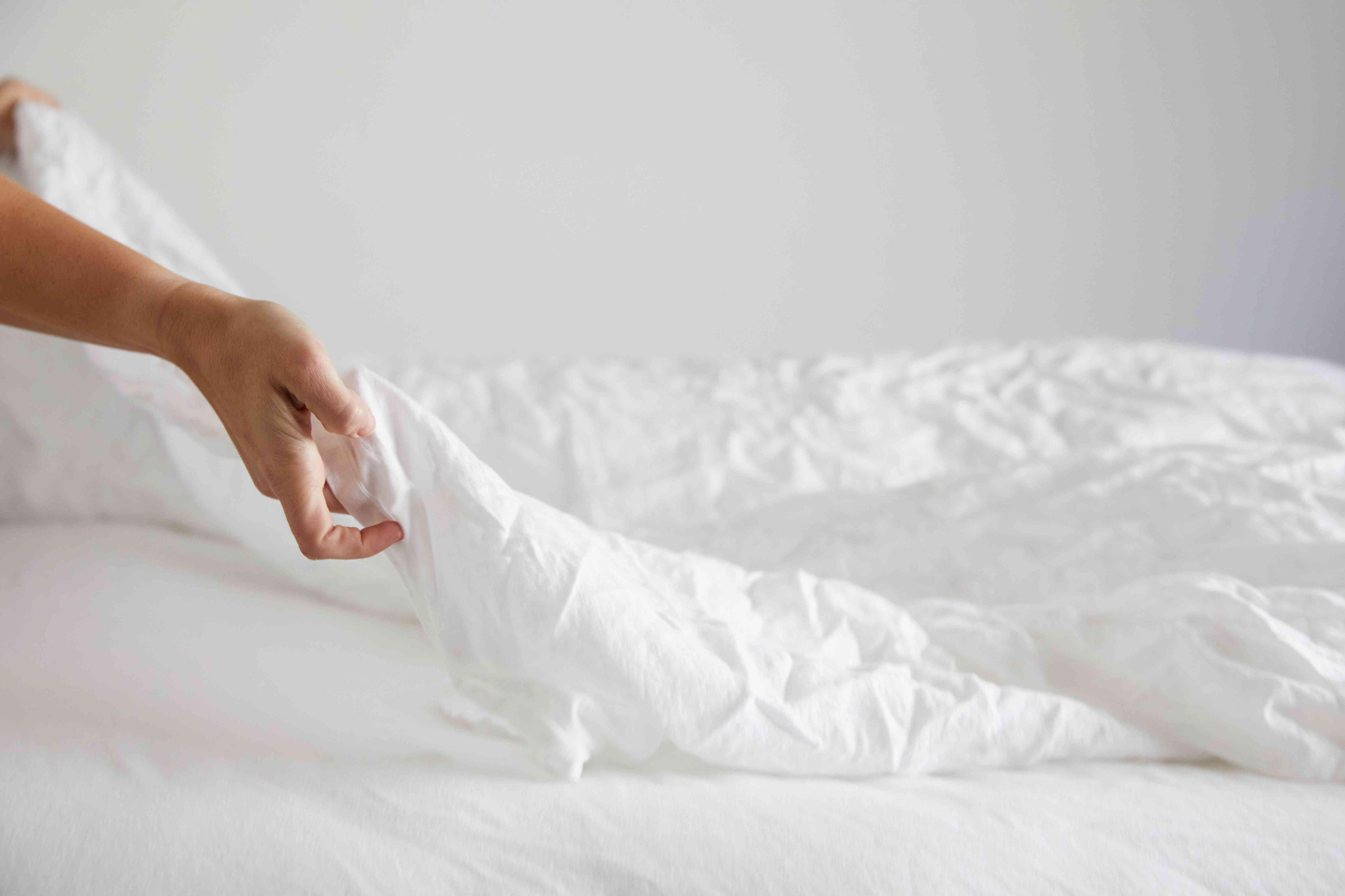 persona quitando la ropa de cama
