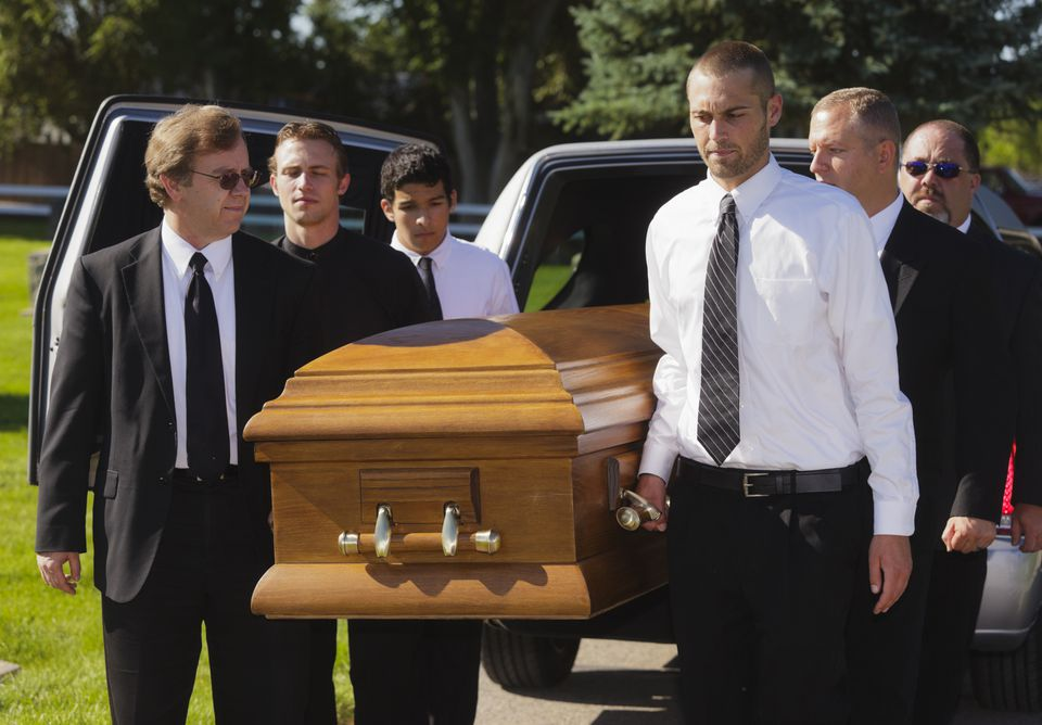 Pallbearers taking a casket out of a hearse