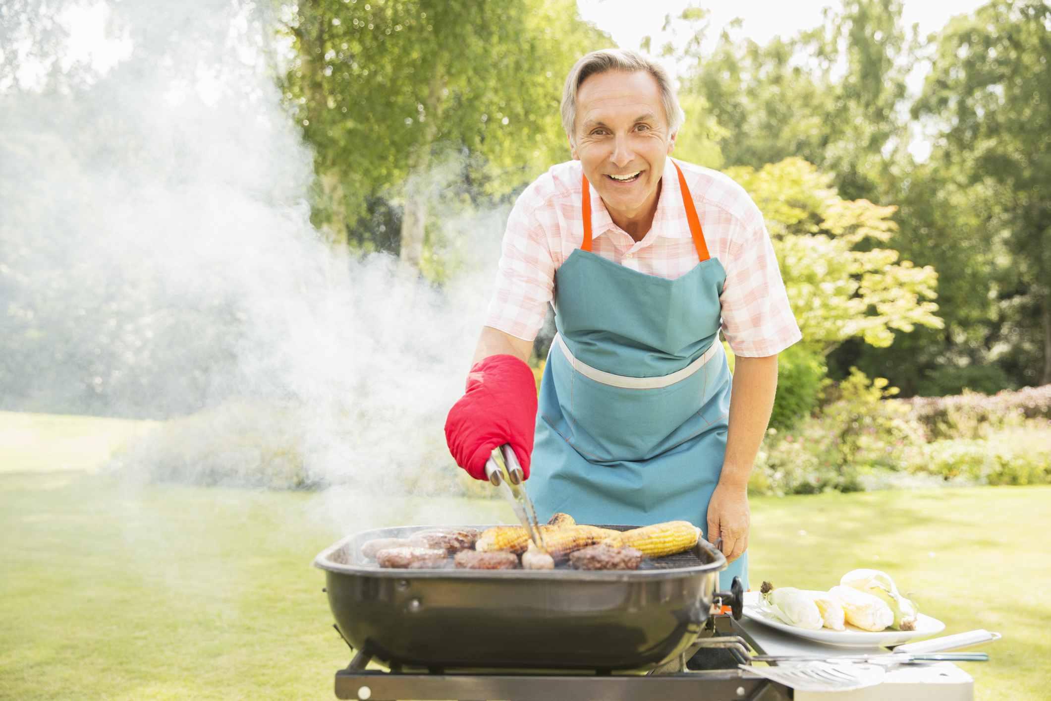 Principal con delantal y manopla de horno para asar alimentos en una parrilla de barbacoa . , Cocina al aire libre con parrilla, encimera y sillas