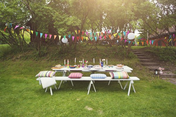 Buntings hanging over food served on decorated picnic table at back yard