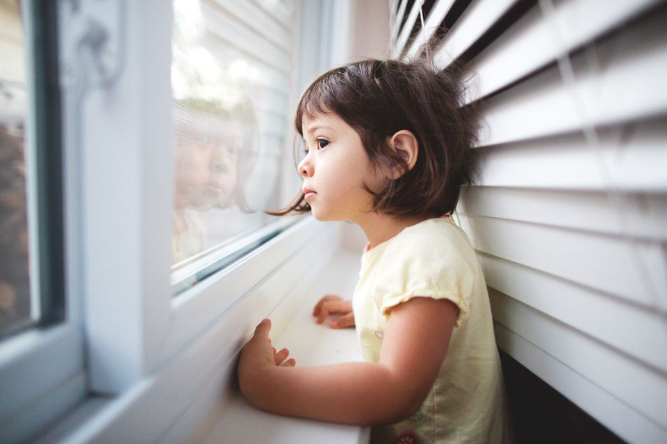 sad Toddler Girl looking out the window