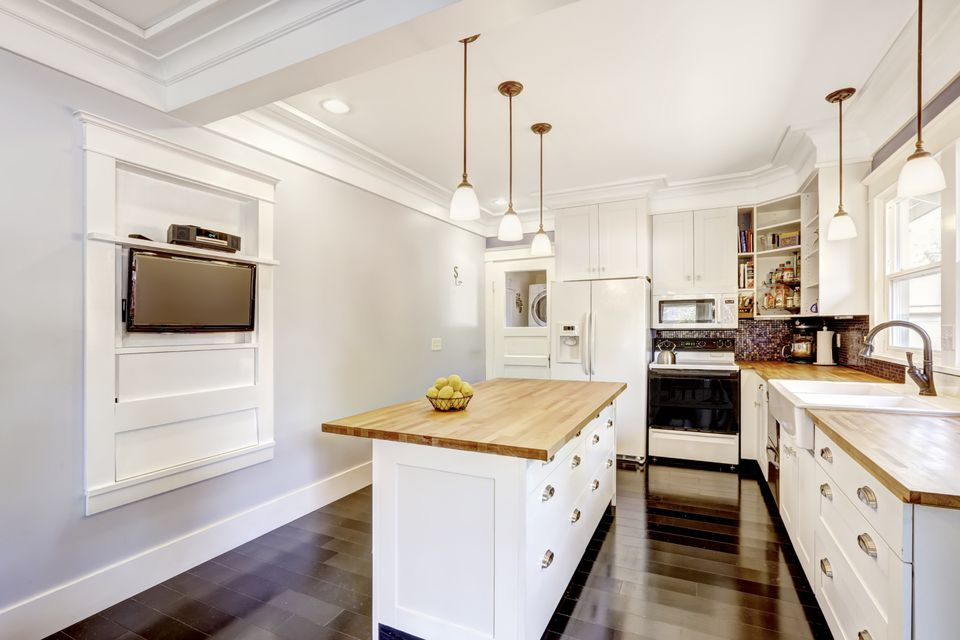 Kitchen interior in white tones with hardwood counter tops.