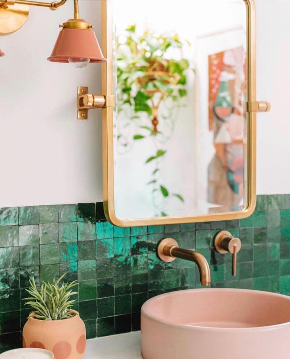Baño con azulejos verdes y lavabo de cemento rosa.