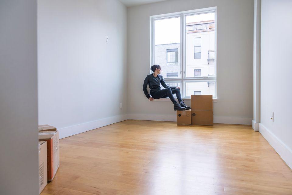 Mudarse a la nueva casa. Adolescente sentado en su futura habitación entre cajas con sus cosas.