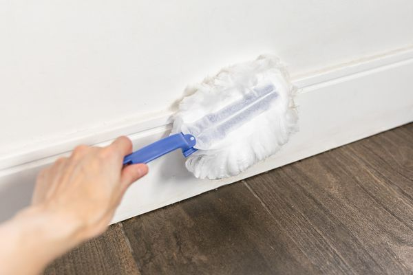 dusting a baseboard