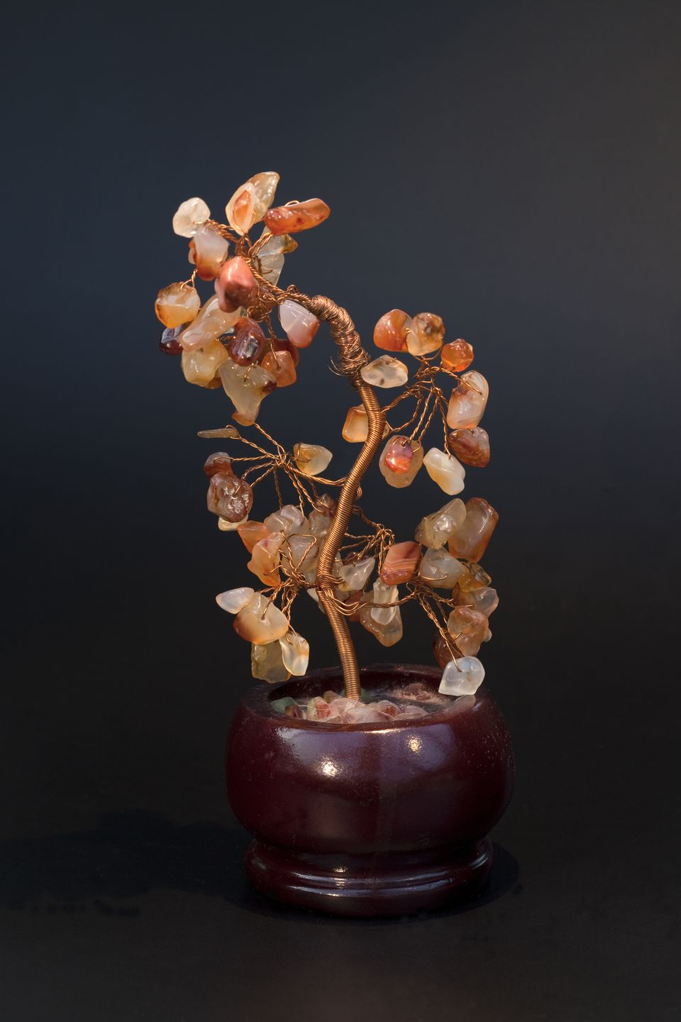 A Carnelian Crystal Tree against a grey background