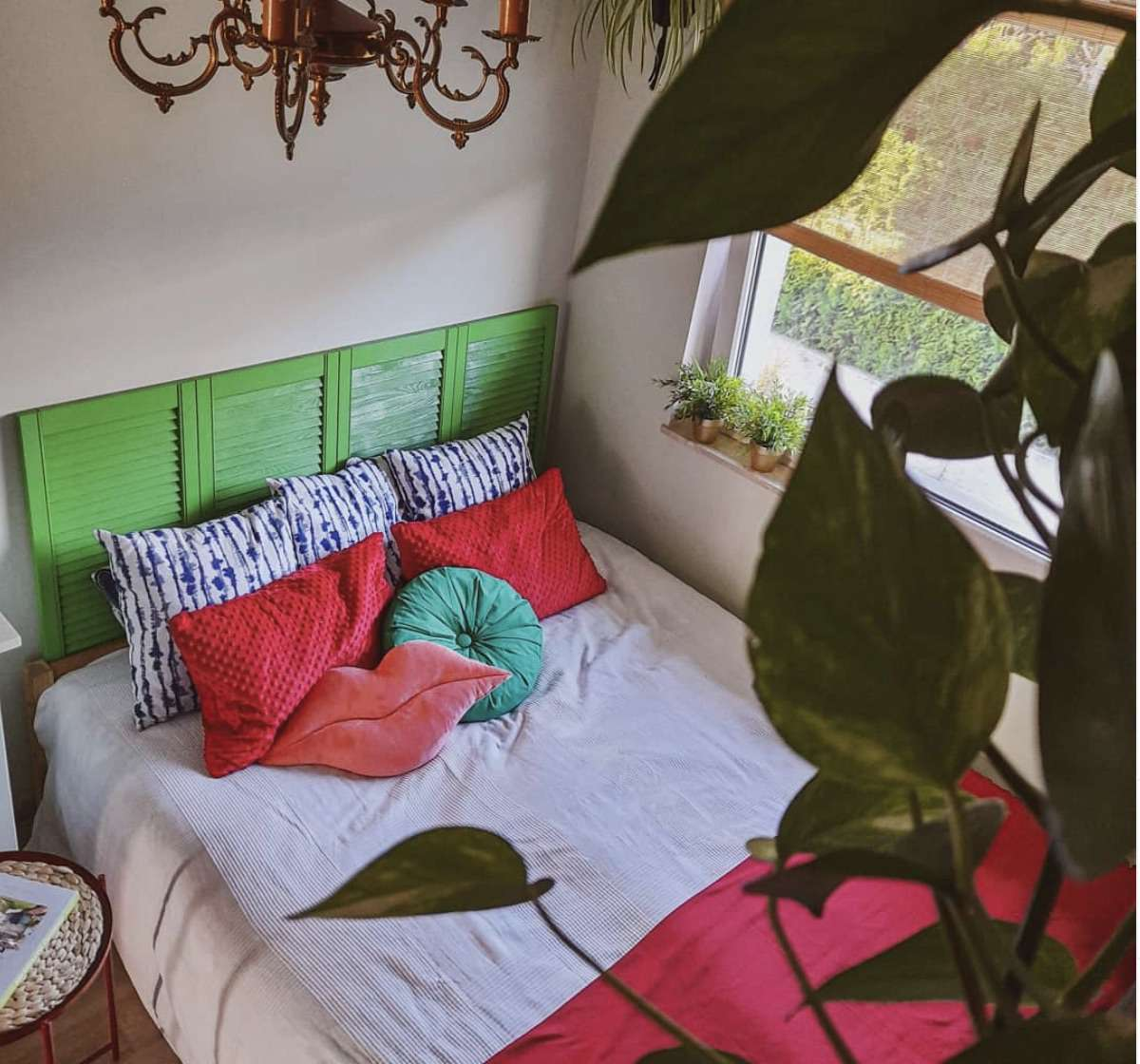 bedroom with bright green headboard and plants, red pillows and blanket, elegant bronze chandlier