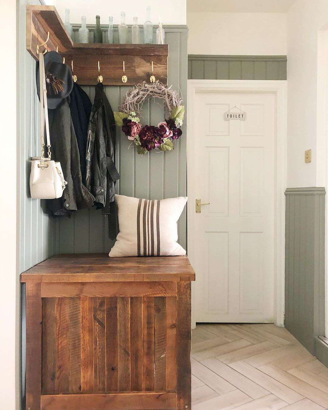 Entryway with green wood paneling