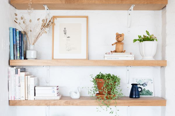 Wooden open shelves styled with books, houseplants and small decor items