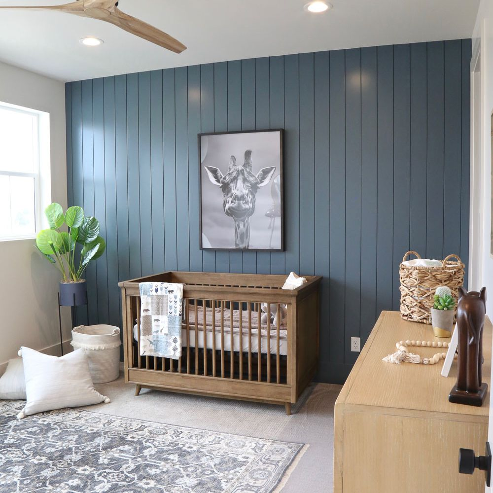 Clean, contemporary nursery with slate blue paneled wall treatment.