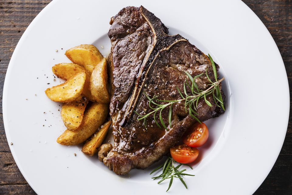 Grilled T-Bone Steak with roasted potato wedges on white plate on wooden background close up