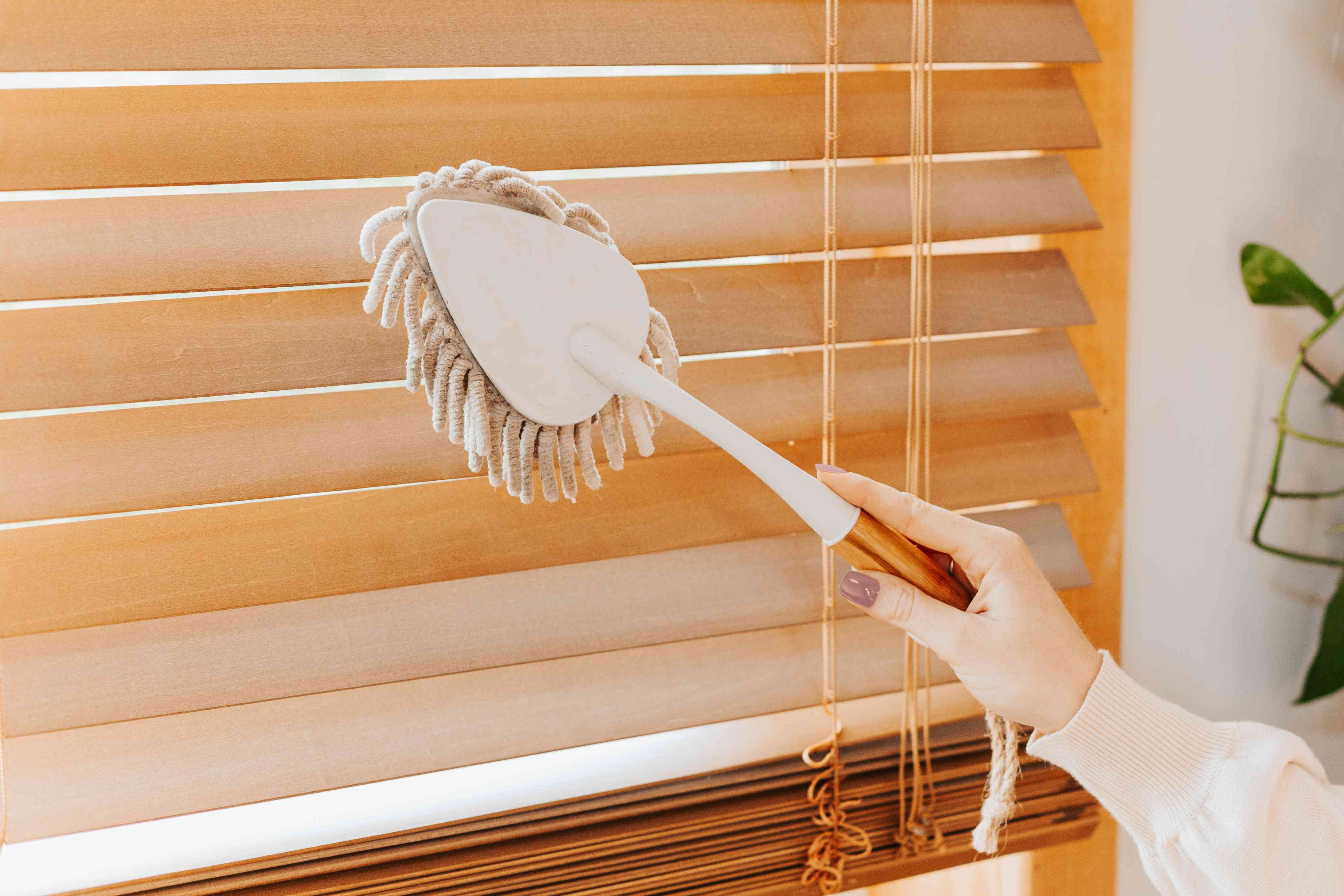 Microfiber duster wiping down wooden blinds