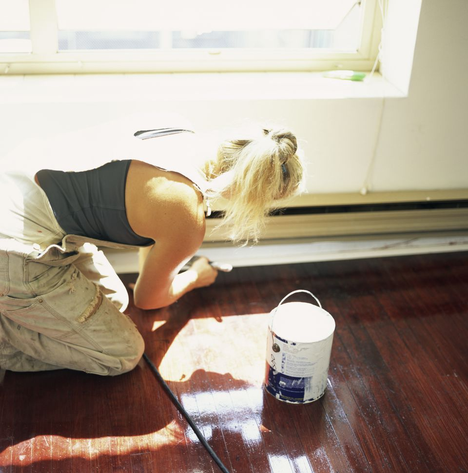 Woman Priming Baseboard Before Painting