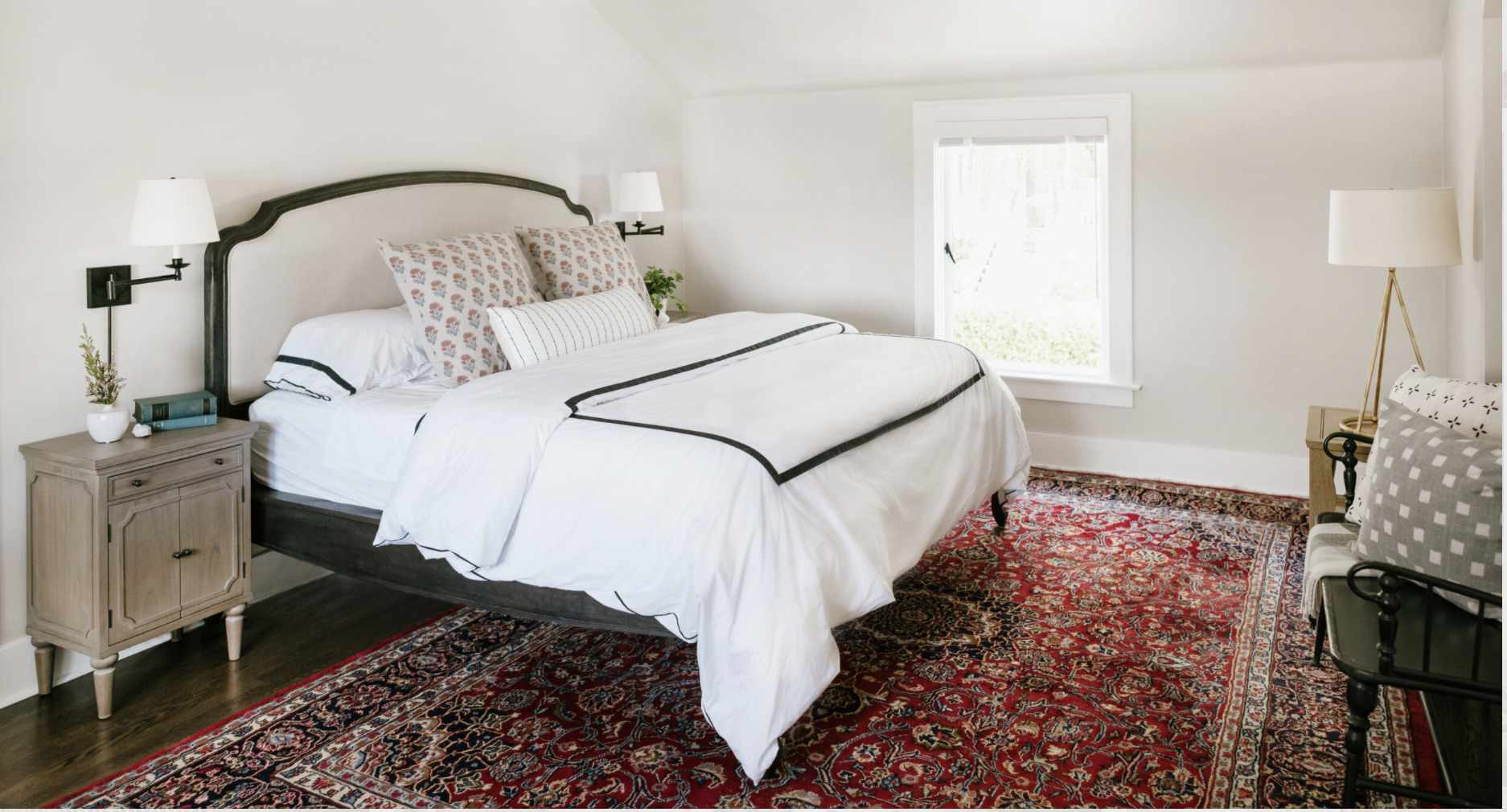 bed room with giant red paisley rug, white color scheme throughout